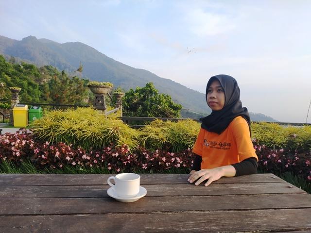 menikmati secangkir kopi pagi dengan view pegunungan yang menawan