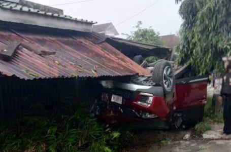 TERGULING : Roda mobil Wuling H-8407-DX tampak berada di atas setelah menabrak pohon dan terguling hingga serta menabrak beranda rumah. (Istimewa)