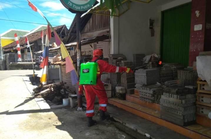 Petugas damkar menyemprotkan cairan desinfektan di lapak pedagang dan lingkungan sekitar pasar.
