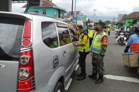 DIBERHENTIKAN: Pengguna jalan diberhentikan untuk mengecek penggunaan masker dalam operasi yang digelar di Jalan Tambaksari Kidul - Dukuhwaluh Kecamatan Kembaran, Minggu (10/5).