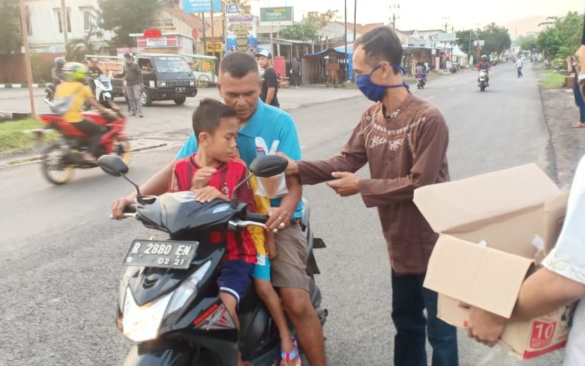 BAGI TAKJIL: Anggota Komunitas King Cimanggu, Raciber bagi-bagi takjil gratis kepada pengguna jalan di Jalan Raya Cimanggu Kecamatan Cimanggu Kabupaten Cilacap.Jum'at (15/5).
