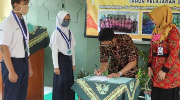 Prosesi penyerahan siswa oleh Kepala SMP Negeri 2 Sidareja Lely Dianawati SPd kepada orang tua siswa secara simbolis diwakili Ketua Komite Sekolah Satrio Sujatmiko SPd MPd. (Foto/TASLIM INDRA/BANYUMAS EKSPRES).