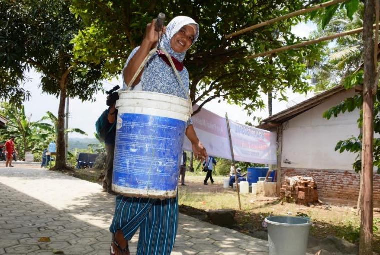 AMBIL AIR : Warga Dusun Danasri Desa Jeruklegi Kulon memikul air bersih yang diambil dari ceruk di aliran sungai Jambu. (Wagino)