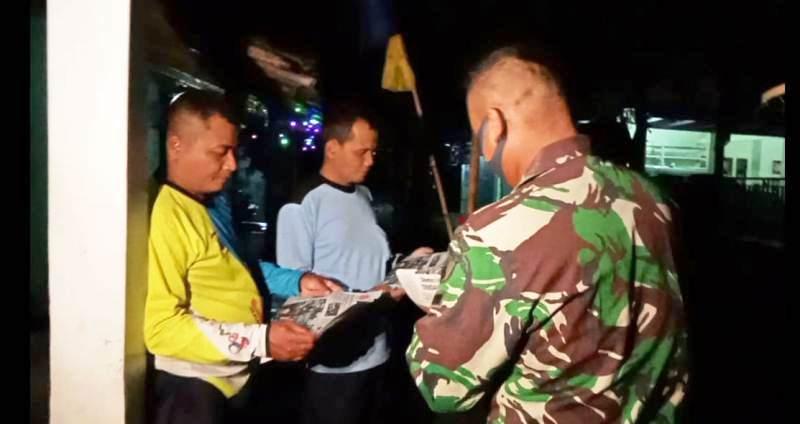 BACA KORAN: Anggota tim teknisi bangunan dari Kodim 0713 Brebes bersama warga tengah membaca surat kabar.