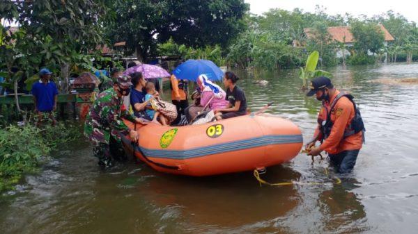 EVAKUASI: Petugas gabungan mengevakuasi warga terdampak banjir dengan menggunakan perahu karet.